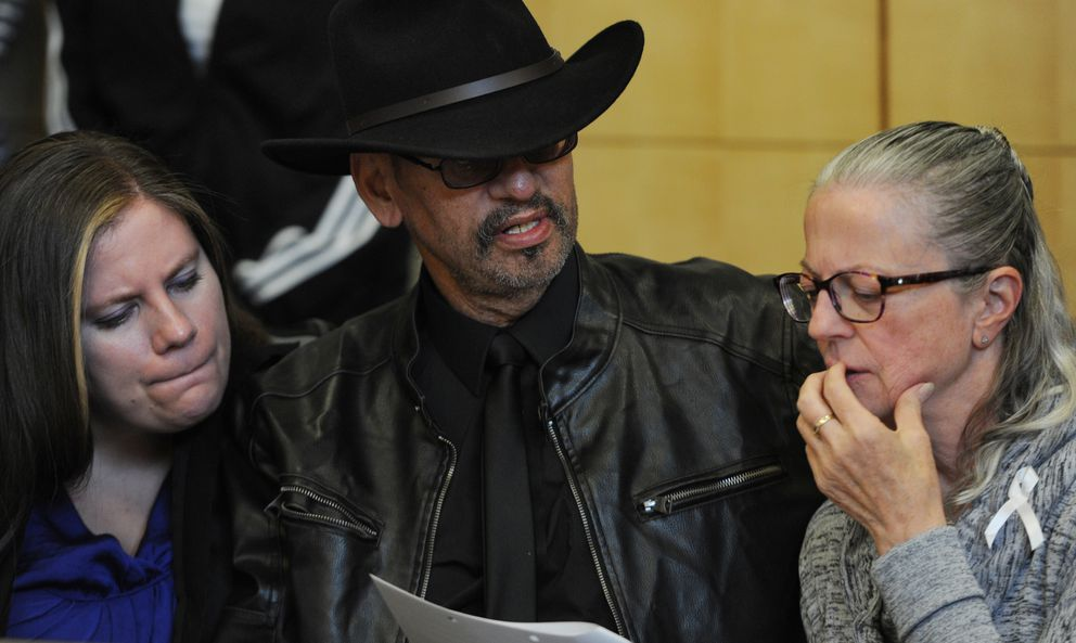 Timothy Hoffman, father of teenager Cynthia Hoffman who was murdered near Thunderbird Falls last week, sits with family friend Lesley Sonnenberg, left, and Cynthia's godmother Michaela Kelly, right, as they read charging documents before the arraignments of Denali Brehmer and and Caleb Leyland in the Anchorage Correctional Complex courtroom on Sunday, June 9, 2019. (Bill Roth / ADN)