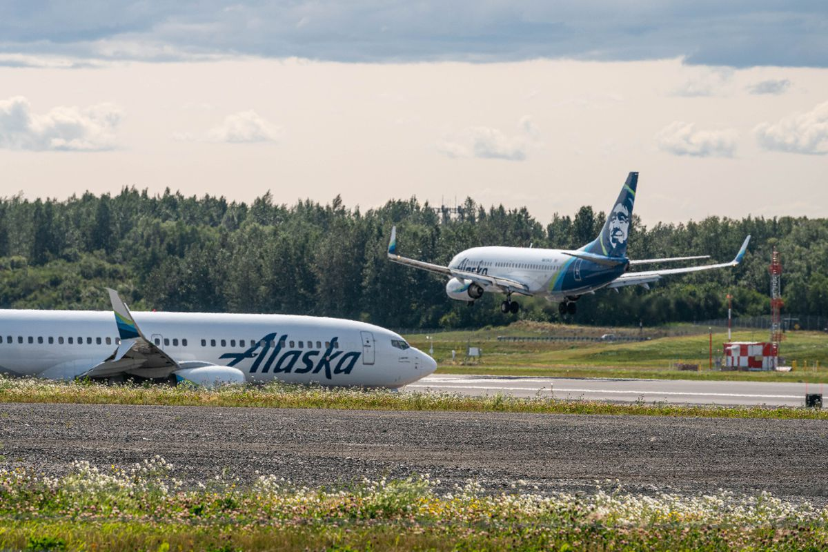 An Alaska Airlines plane lands while another waits to take off on Thursday, July 30, 2020 at the Ted Stevens Anchorage International Airport. (Loren Holmes / ADN)