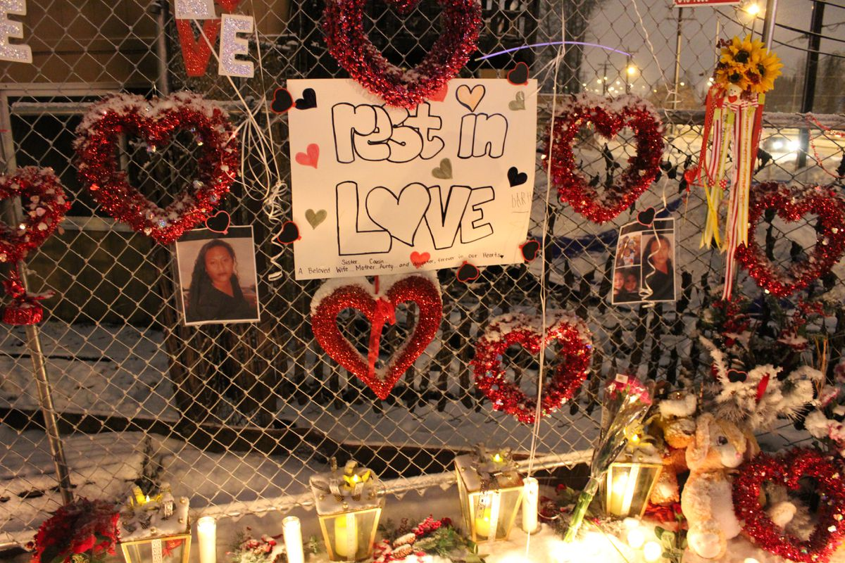 Family and friends decorated the fence behind the Royal Suite Apartments with pictures of 38-year-old Teuaililo Nua, a mother of two girls who died, her husband said, after jumping out of their third-story apartment window. (Jerzy Shedlock / Alaska Dispatch News)