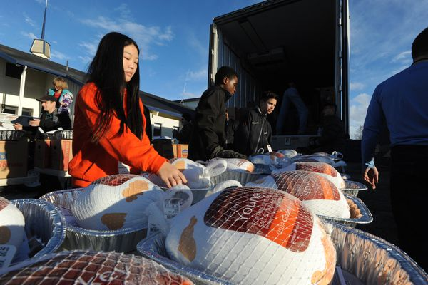 Volunteers Maya Farley, 13, Eugene Mulinde, 12, and Zach Budd, 13, from Pacific Northern Academy helped distribute frozen turkeys at the Mt. View Community Center during the annual Thanksgiving Blessing holiday meal distribution on Monday, Nov. 19, 2018. The Food Bank of Alaska, its partners, and volunteers from the faith-based community helped distributed groceries for an entire Thanksgiving meal to an estimated 10,000 families in need in Anchorage on Monday and the Mat-Su Valley on Saturday. (Bill Roth / ADN)