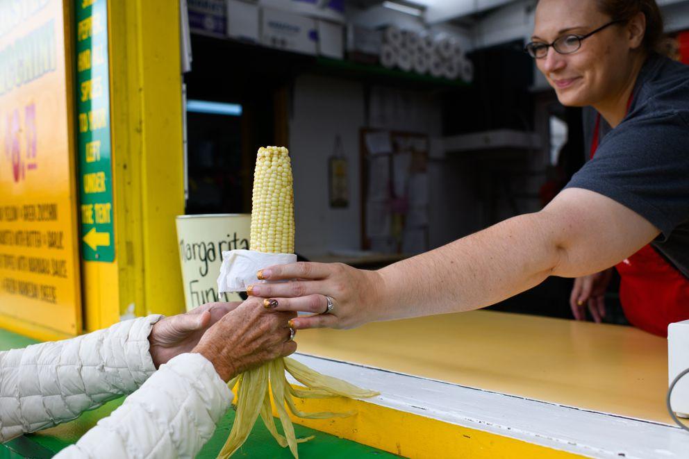 Nikki Blazka serves an ear of corn at Friar Tuck's at the Alaska State Fair on August 28, 2018. (Marc Lester / ADN)