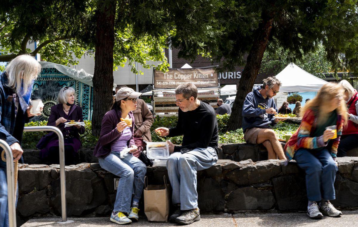 Mostly unmasked people eat lunch at the Eugene Saturday Market in Eugene, Ore., on May 8, 2021. Washington Post photo by Melina Mara.