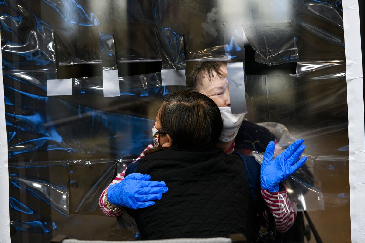 Cordelia Scott, facing, hugs her daughter-in-law, Pheng Scott, through a sheet of plastic at Aspen Creek, an assisted living center, on December 2, 2020. This was the second session of the