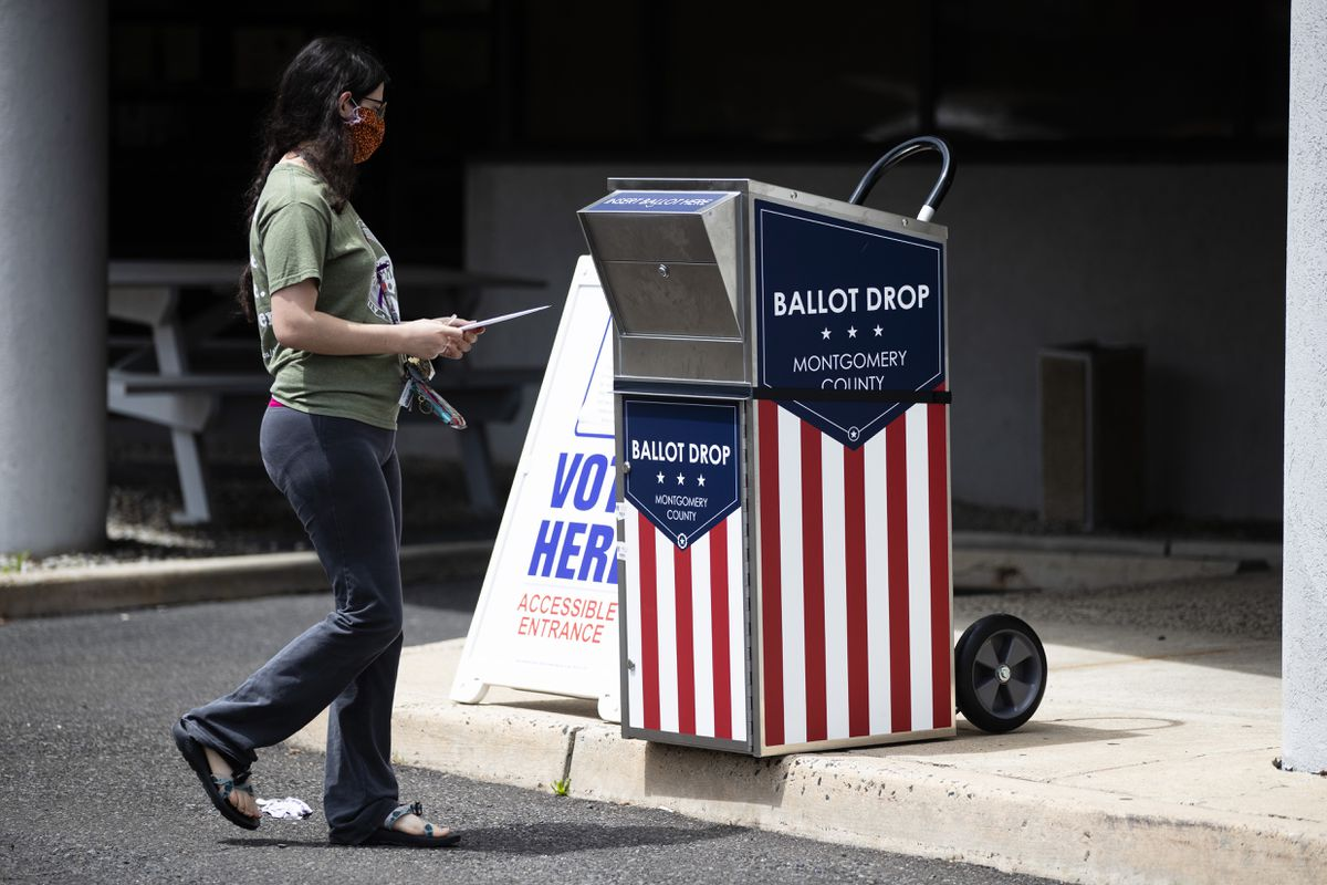 A voter drops off their mail-in ballot prior to the primary election, in Willow Grove, Pa., Wednesday, May 27, 2020. (AP Photo/Matt Rourke)