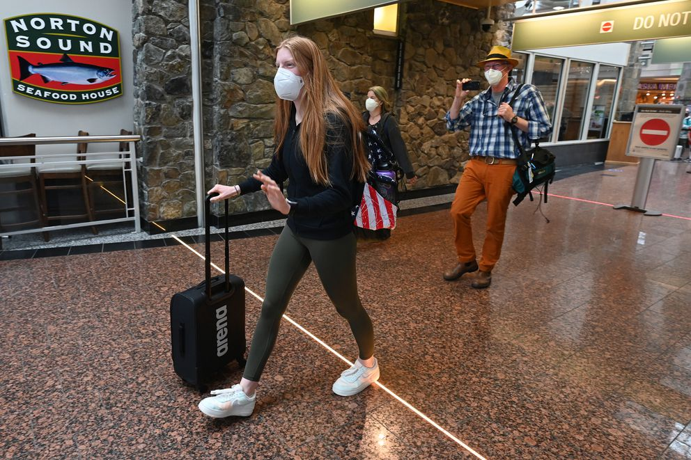 Swimmer Lydia Jacoby, followed by her mother Leslie and father Rich Jacoby, arrives in Anchorage eight days after making the U.S. Olympic swim team. (Bill Roth / ADN)