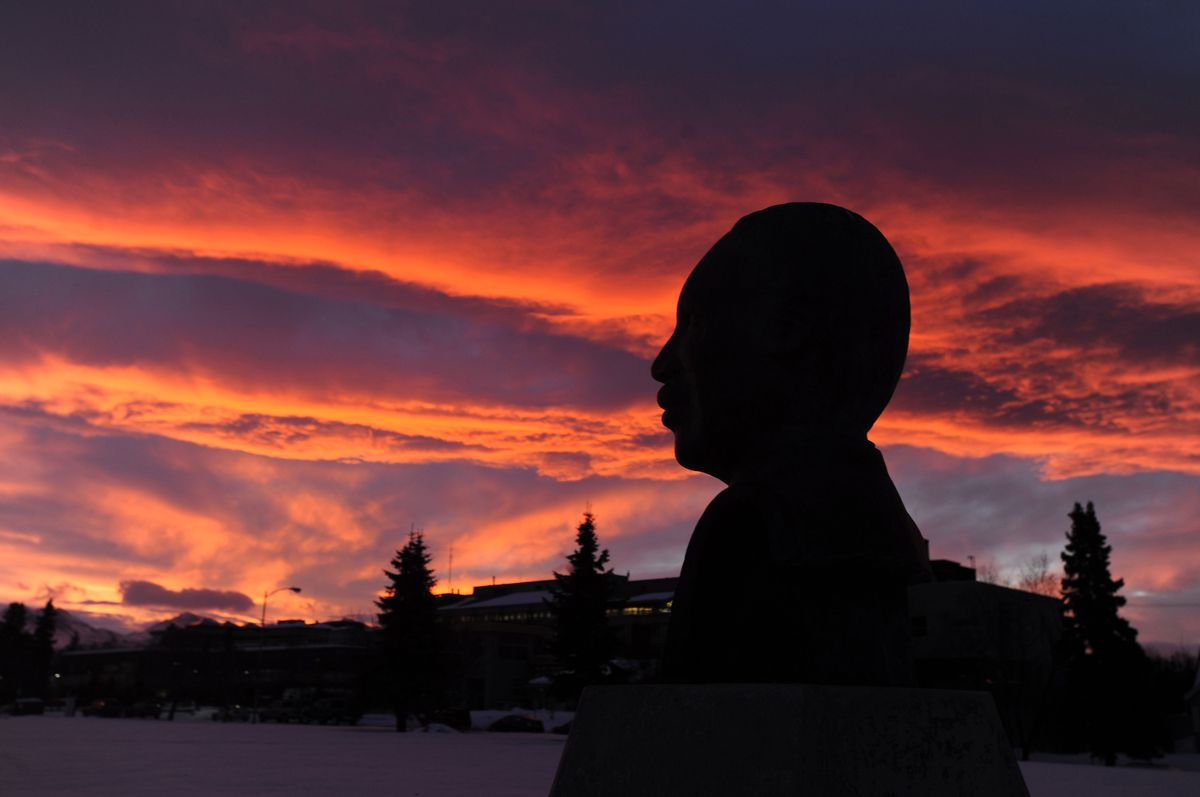 A stunning sunrise greets the bust of Dr. Martin Luther King, Jr. at his Anchorage memorial as the holiday honoring him dawns on Monday, January 20, 2014, on the Delaney Park Strip.