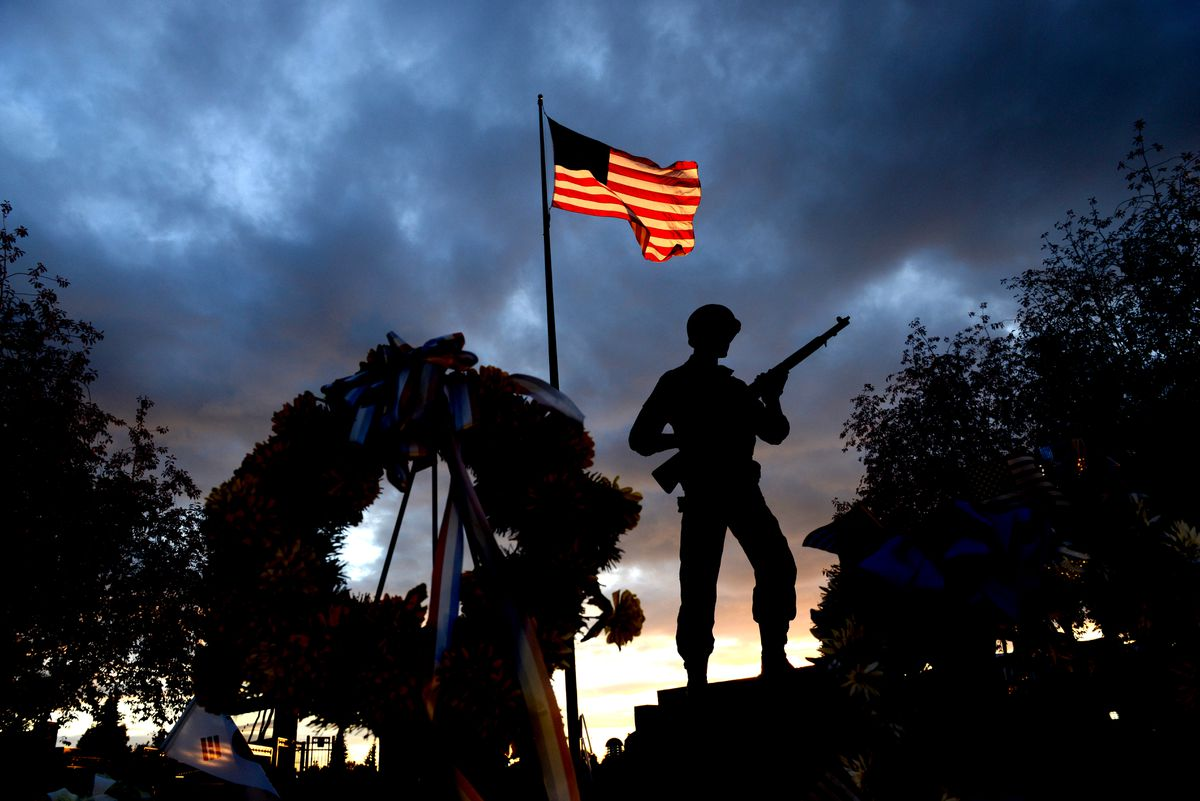 The setting sun lights the American flag at the Anchorage Veteran's Memorial on the Park Strip in Anchorage, Alaska on Sunday Aug. 27, 2017. (Bob Hallinen / ADN)