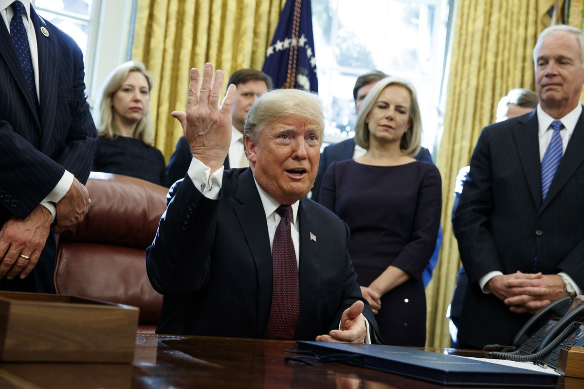 President Donald Trump answers a reporters question about the investigation of special counsel Robert Mueller during a signing ceremony of the