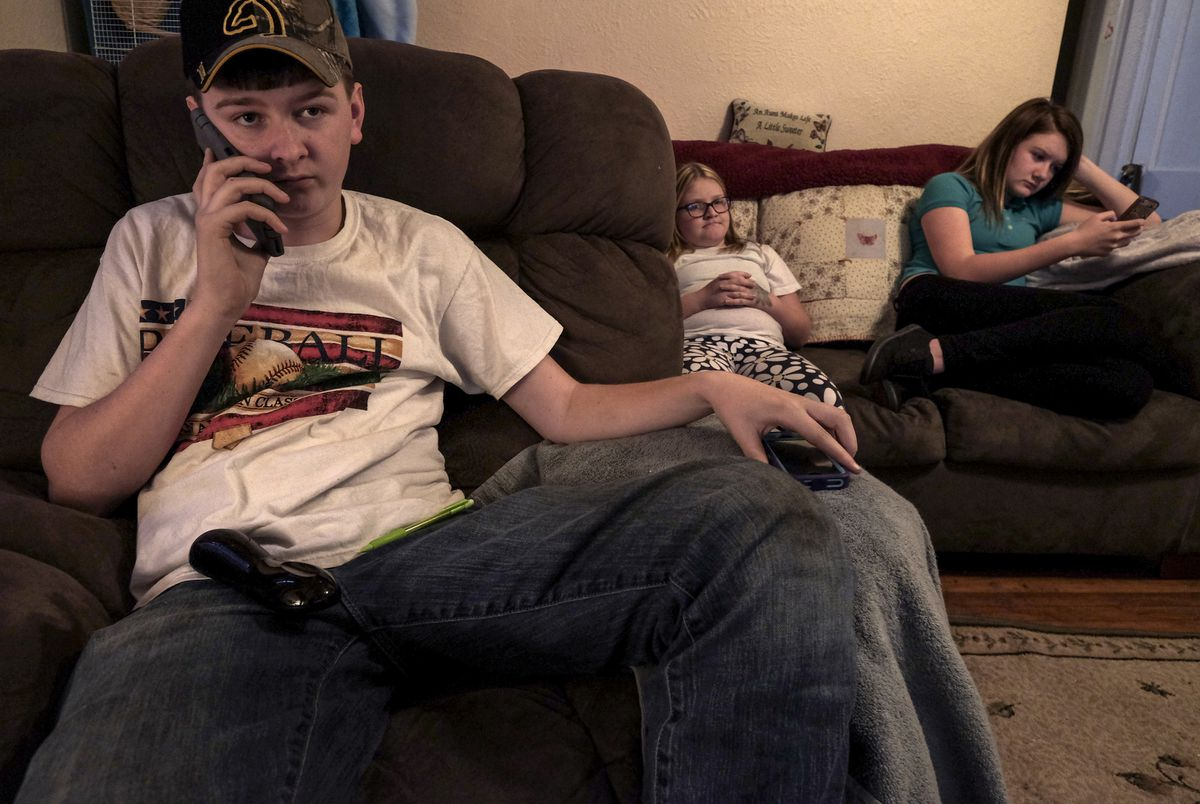 The Pulliam siblings, Zaine, 17, Zoie, 10, and Arianna, 13, hang out in the living room of their home in South Charleston, W.Va. The trio lost their parents, Austin and Amanda, on Easter 2015. The couple died of heroin overdoses. (Bonnie Jo Mount / The Washington Post)