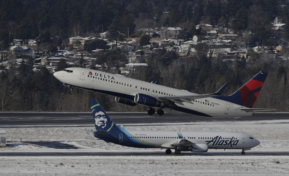 A Delta Air Lines plane takes off above a taxiing Alaska Airlines plane, Tuesday, Feb. 5, 2019, on a snow-bordered runway at Seattle-Tacoma International Airport in Seattle. (AP Photo/Ted S. Warren)