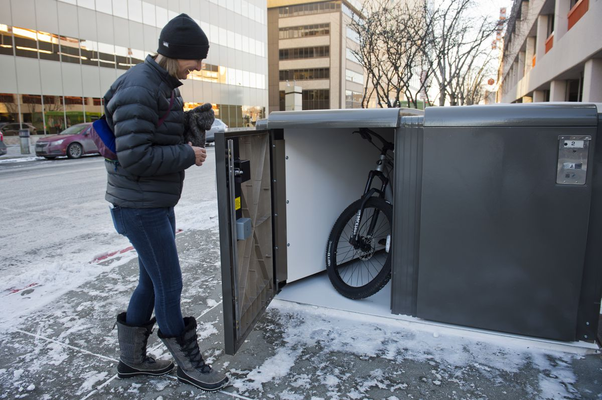 Katie Bledsoe shows the AK Bikebox locker at the corner of 7th Avenue and G Street in downtown Anchorage on February 13, 2020. Bledsoe and her husband Justin Bledsoe own the business, which has just this location so far. (Marc Lester / ADN)