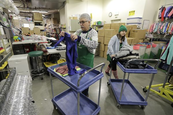 In this Friday, Dec. 21, 2018, photo, Chris Meyer, left, and Maddi Heim, fold and sort donated clothes at Treehouse, a nonprofit organization in Seattle that serves the needs of children in the foster-care system. The charity was one of several that received donations from the $11 million secret estate of Alan Naiman -- a social worker who died from cancer earlier in 2018 after living a private life of frugality and concern for children facing hardship. (AP Photo/Ted S. Warren)