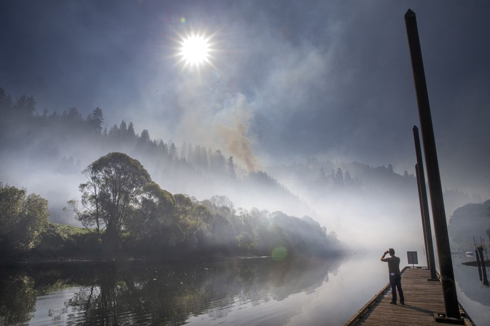 Smoke hangs over the Siuslaw River near Mapleton, Ore., as the The Sweet Creek Milepost 2 Fire burns on the hillside overlooking the town, Tuesday, Sept. 1, 2020. (Chris Pietsch/The Register-Guard via AP)