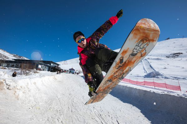 Jason Borgstede does a trick on the halfpipe during the Merry Marmot festival on Saturday, March 30, 2019 at Arctic Valley. Borgstede owns Blue & Gold Boardshop, which organized the retro-themed snowboard event. (Loren Holmes / ADN)