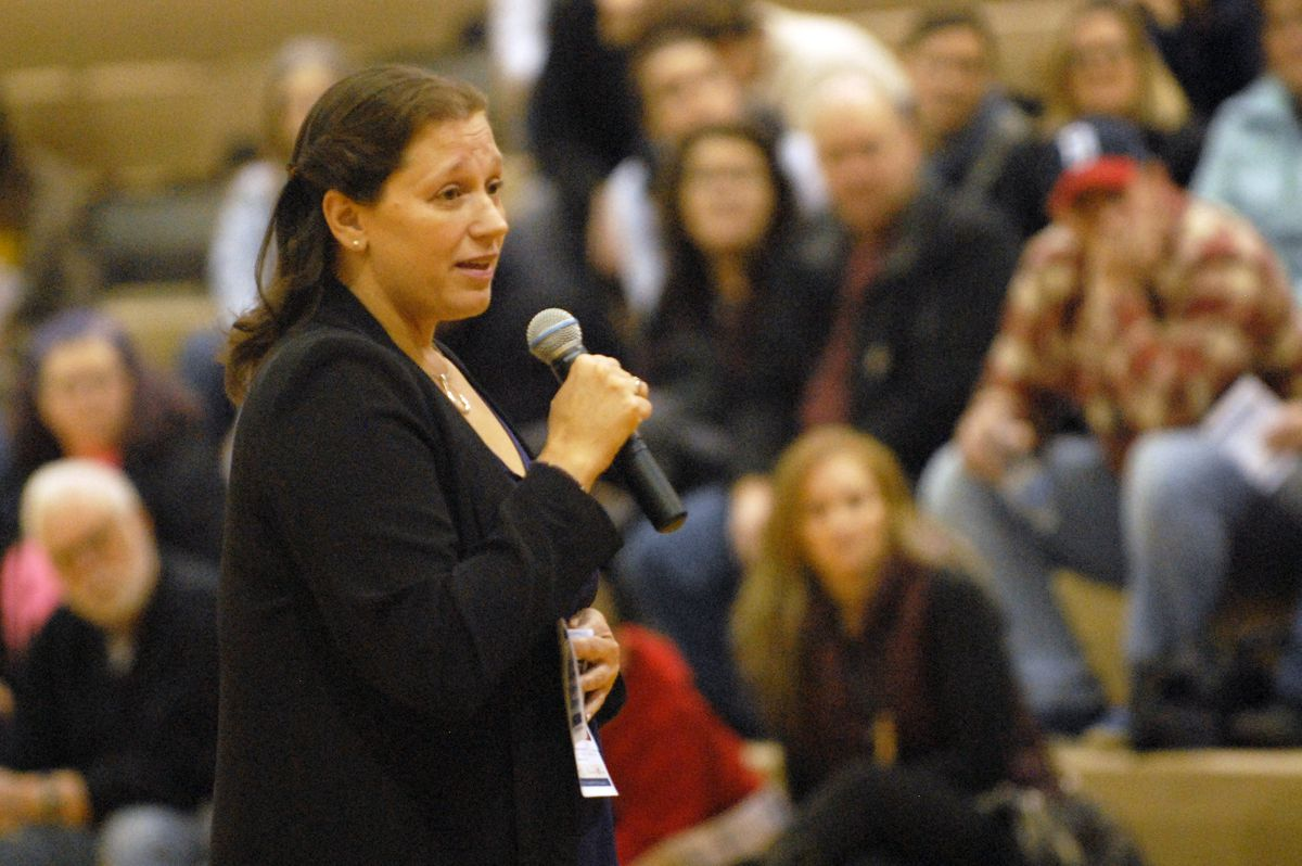 Anchorage School Board member Elisa Snelling talks to the crowd at the beginning of a public meeting on the future of secondary education in Eagle River on Tuesday, Feb. 12, 2019 at Chugiak High School. (Matt Tunseth / Chugiak-Eagle River Star)