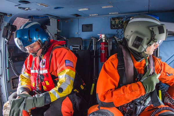 Aviation Survival Technician Micah Franklin, left, and Aviation Maintenance Technician Kyle Stalter are part of a crew of four aboard a Coast Guard Jayhawk helicopter during a flight flight near Prudhoe Bay on October 10.