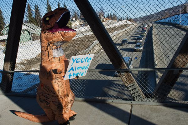Theresa Bundy wore a dinosaur costume and held a sign that said