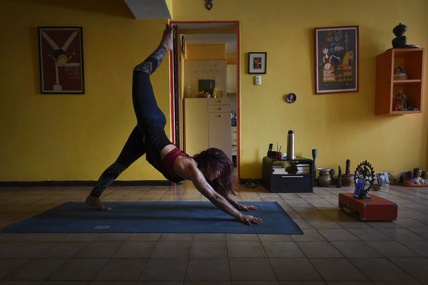 Instructor Lu Gomez leads an online yoga class from her home in Caracas, Venezuela, April 18, 2020, during a government-imposed quarantine to help curb the spread of the new coronavirus. (AP Photo/Matias Delacroix)
