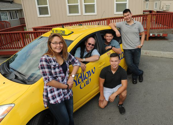 Mark Braudis sits in the driver's seat of his cab as his kids Kelly, David, Stephen and Michael Braudis surround him. (Bob Hallinen / Alaska Dispatch News)