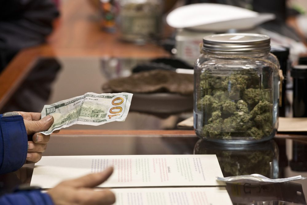 A customer pays for a purchase at Herbal Outfitters on opening day. Marijuana retailer Herbal Outfitters opened its doors to customers for the first time in Valdez on Saturday, October 29, 2016. (Marc Lester / ADN)