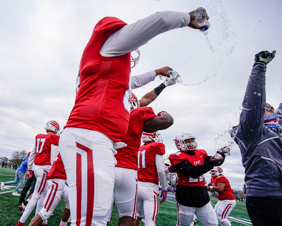 East players dump water on their coach after winning the city championship football game. (Loren Holmes / ADN)