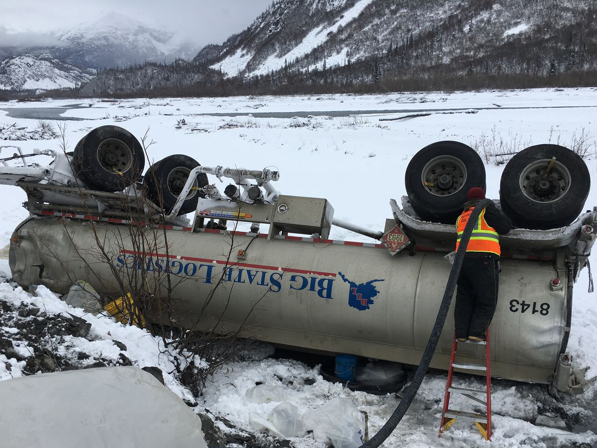 Big State Logistics response crew offloading fuel from a rolled and damaged secondary tank, Mile 42 of the Richardson Highway. Tsaina River bank is in the background. Oct. 21, 2016. (Photo / ADEC)