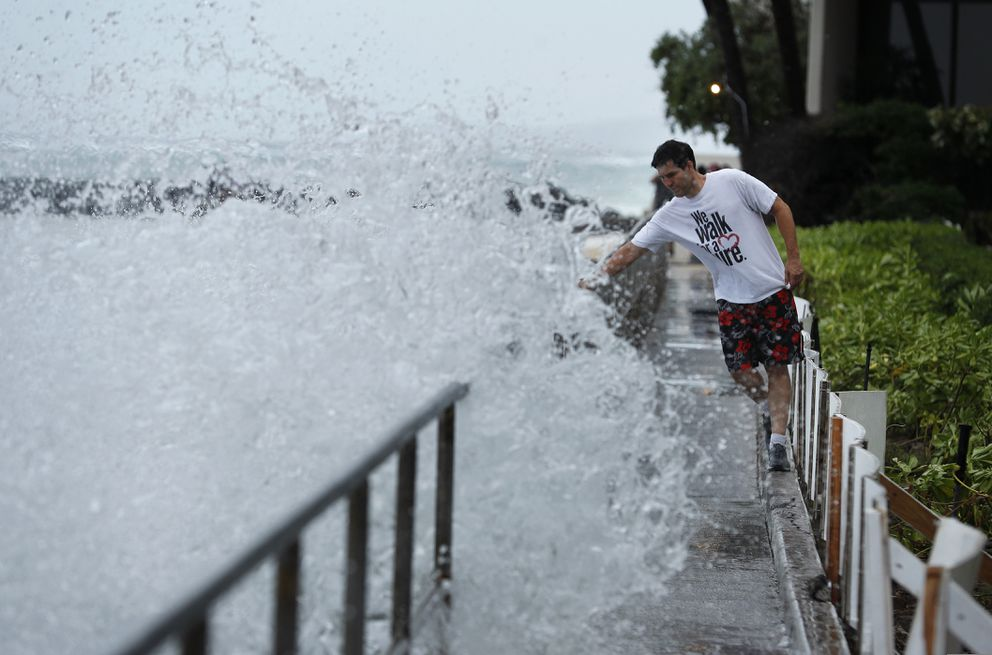 A man avoids getting splashed by a large wave on a walkway along a beach ahead of Hurricane Lane, Thursday, Aug. 23, 2018, in Honolulu. (AP Photo/John Locher)