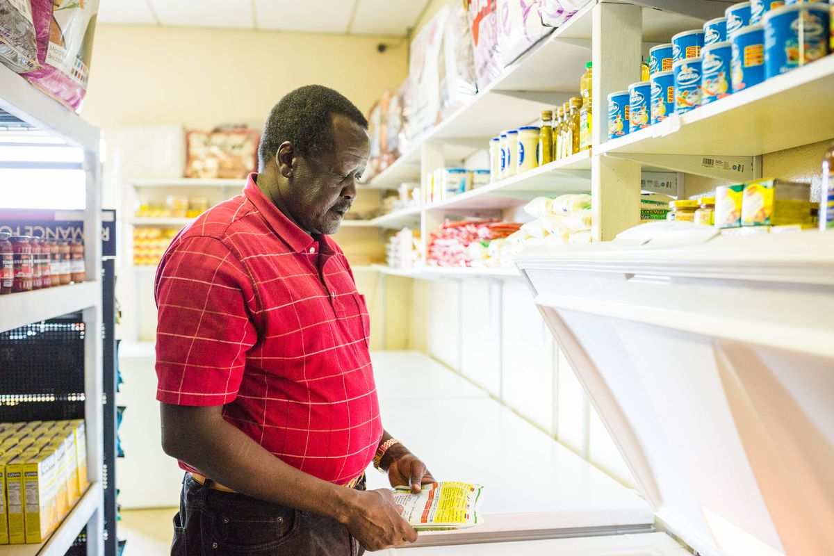In South Sudan, William Riek performed eye surgery and practiced dentistry. Today he works at an ethnic grocery in East Anchorage, a center of the Sudanese community, while raising four children of his own. Photographed at Banadir Halal Market on Wednesday, Aug. 24, 2016. (Loren Holmes / Alaska Dispatch News)