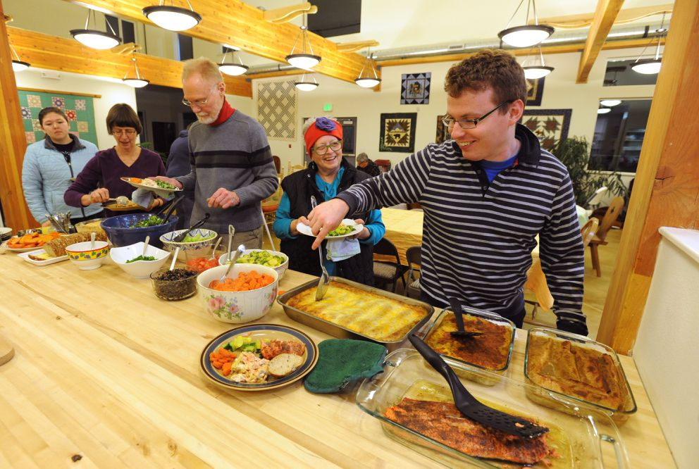 Ian Miner, right, fills his plate as resident and guests gather for dinner on Dec. 8, in the common house at Ravens' Roost, Anchorage's first cohousing community of privately owned homes. (Bill Roth / Alaska Dispatch News)