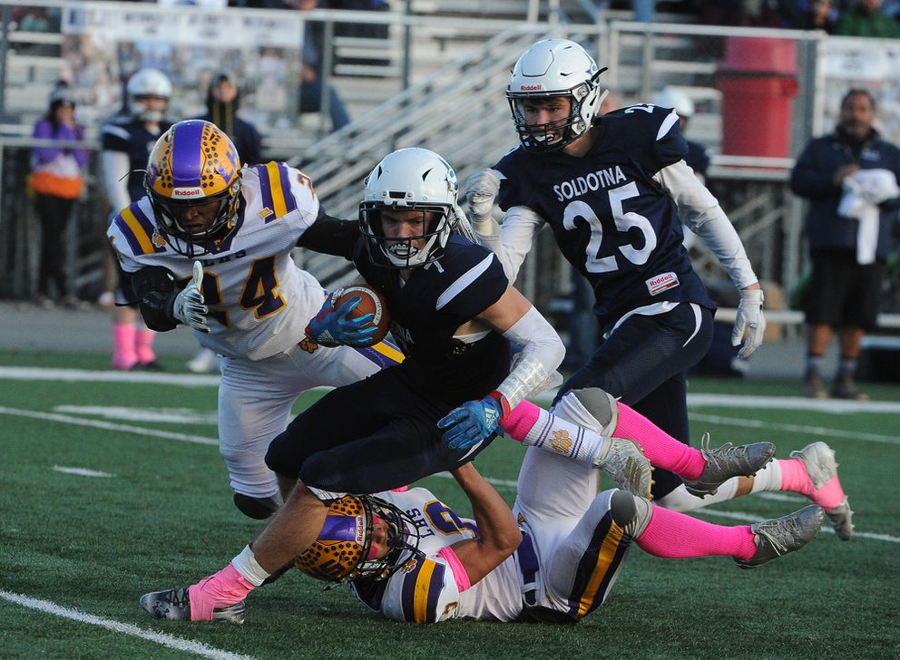 Jhon Rones, of Lathrop High, brings down Soldotna ball carrier Wyatt Medcoff. Andre Williams of Lathrop, and William Simmons, of Soldotna High, were in on the play. (Bob Hallinen photo)