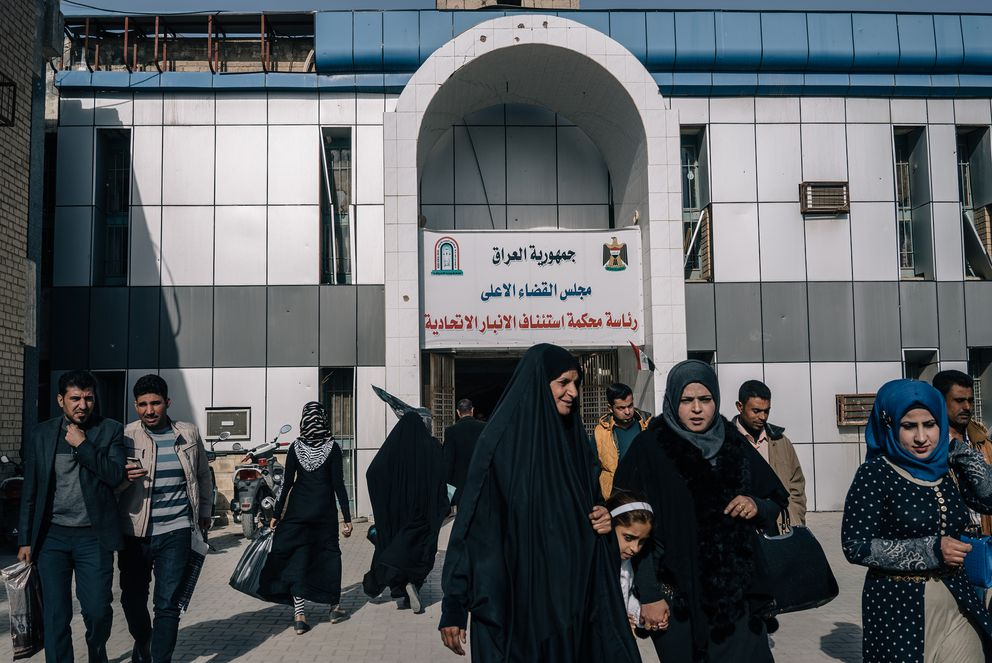 Civilians are seen outside the building of the Court of Appeals in Ramadi. (Photo for The Washington Post by Alice Martins)