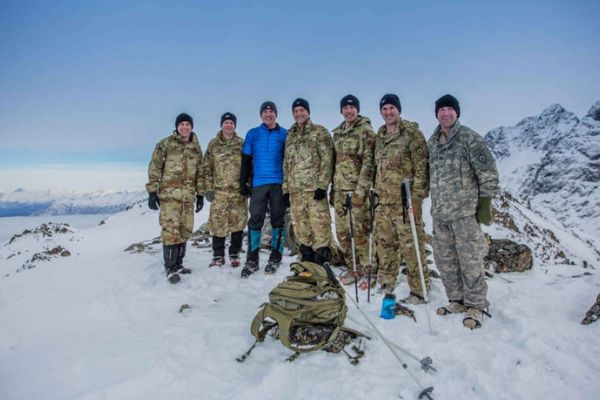 Kirk Alkire (in blue) poses with a group of soldiers atop Gold Star Peak near Eklutna Lake. The 4,148-foot peak was named in honor of the families of fallen service members. (Photo courtesy of Kirk Alkire/Gold Star Peak Alaska)