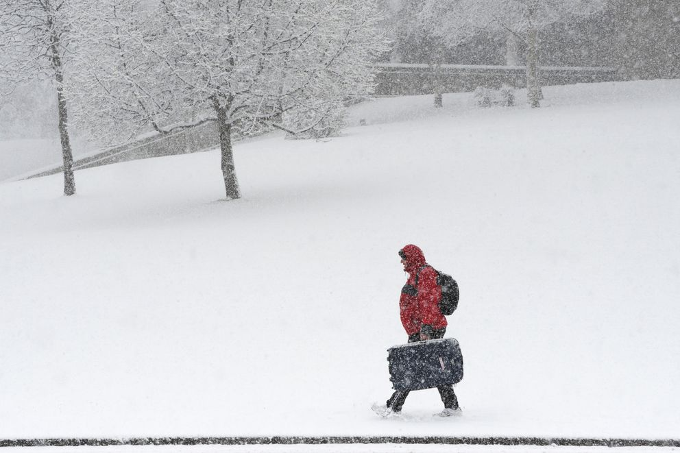 A pedestrian walks along 36th Avenue during a spring snowstorm on Monday, April 22, 2019. (Bill Roth / ADN)