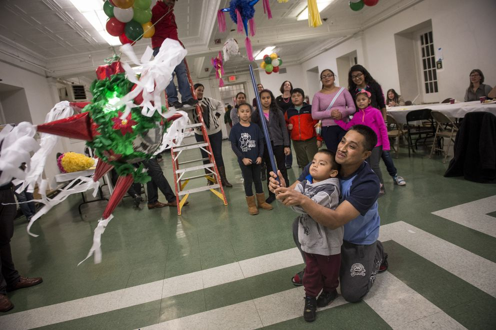 Javier Flores Garcia, who entered the U.S. illegally from Mexico, helps his son Yael, 2, hit a pinata during a celebration at the Arch Street United Methodist Church, in downtown Philadelphia, Dec. 16. (Charles Mostoller/The New York Times)