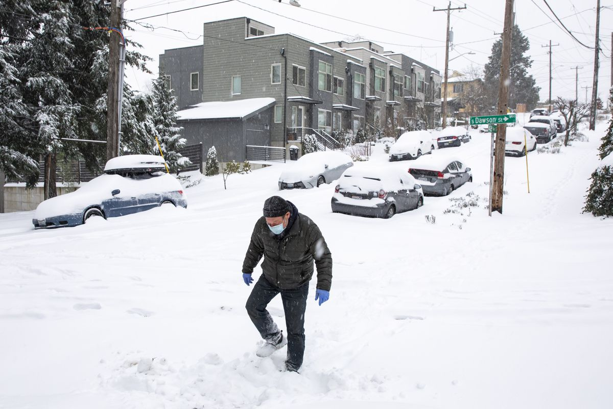 John Kramer walks down 42nd Avenue South in Columbia City as heavy snow blankets the Seattle area Saturday Feb. 13, 2021. (Bettina Hansen/The Seattle Times via AP)