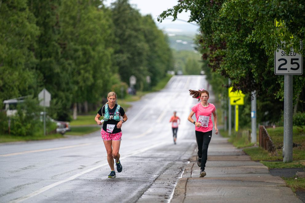 Angie Meahan, left, and Emily Moore run toward the halfway point of Saturday's virtual race. Meahan is holding a map of the course; Moore ran without one and said she followed Meahan. (Loren Holmes / ADN)
