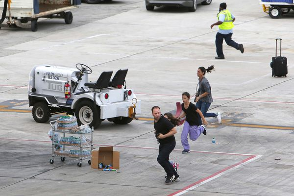 People take cover on the tarmac as authorities said multiple people have died after a lone suspect opened fire at the Ft. Lauderdale-Hollywood International Airport on Friday, Jan. 6, 2017, in Fort Lauderdale, Fla. (David Santiago/El Nuevo Herald/TNS)