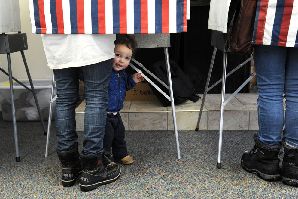 Wesley Kim, 16 months, accompanies mom Callie Kim to the voting booth on Tuesday morning, April 4, 2017, at Turnagain United Methodist Church. (Erik Hill / Alaska Dispatch News)