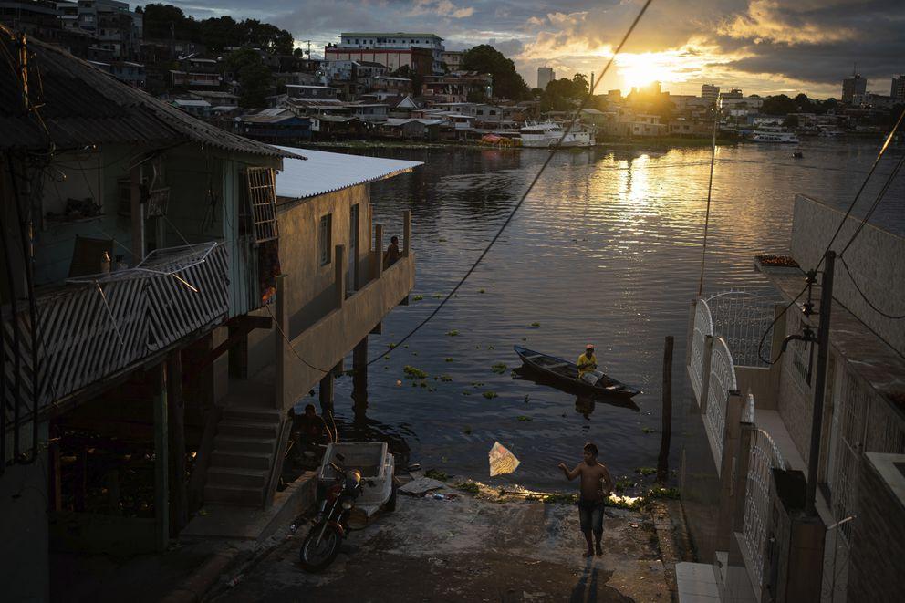 A boy flies a kite by the riverside in Manaus, Brazil, Sunday, May 24, 2020. Per capita, Manaus is Brazil's major city hardest hit by COVID-19. (AP Photo/Felipe Dana)
