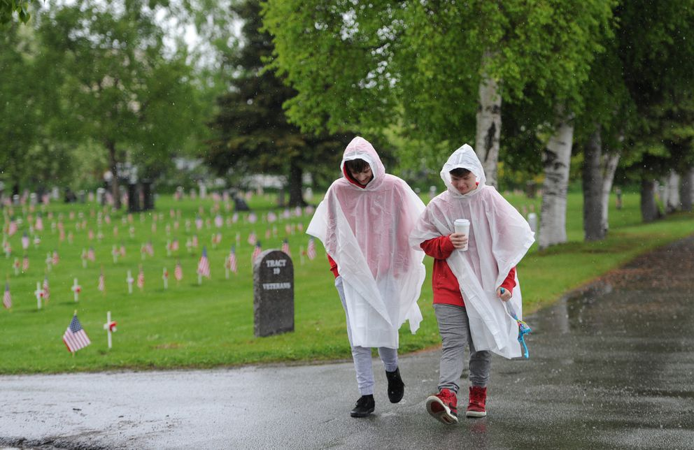 Hunter Ashe and Anthony Felicetty, both 13, helped place American flags at the graves of veterans buried at the Anchorage Memorial Park Cemetery on Sunday, May 26, 2019. (Bill Roth / ADN)