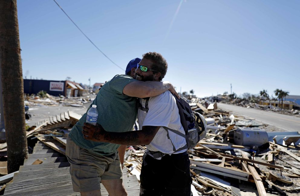 Hector Morales, left, is hugged by friend Matthew Goss, a fisherman, as they reunite after Hurricane Michael which destroyed Morales' home and Goss' boat in Mexico Beach, Fla., Friday, Oct. 12, 2018. (AP Photo/David Goldman)