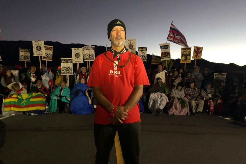 FILE - In this Monday, July 15, 2019, file photo, Dexter Kaiama, foreground, joins demonstrators gathered to block a road at the base of Mauna Kea, Hawaii's tallest mountain. For activists who say they're protecting Mauna Kea, the fight against the proposed Thirty Meter Telescope is a boiling point in Hawaiian history. (AP Photo/Caleb Jones, File)