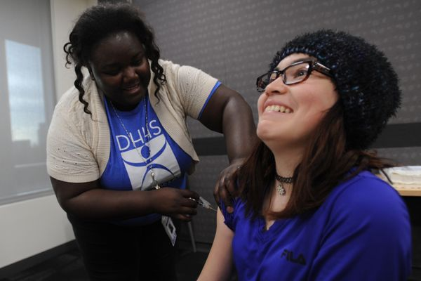 Public health nurse Willy Mamtchueng gives a flu shot to Marissa Crabtree, 12, at the Loussac Library on Tuesday, Oct. 10, 2017. People can walk in for flu shots at the city Public Health Clinic located at 825 L Street. Crabtree said,