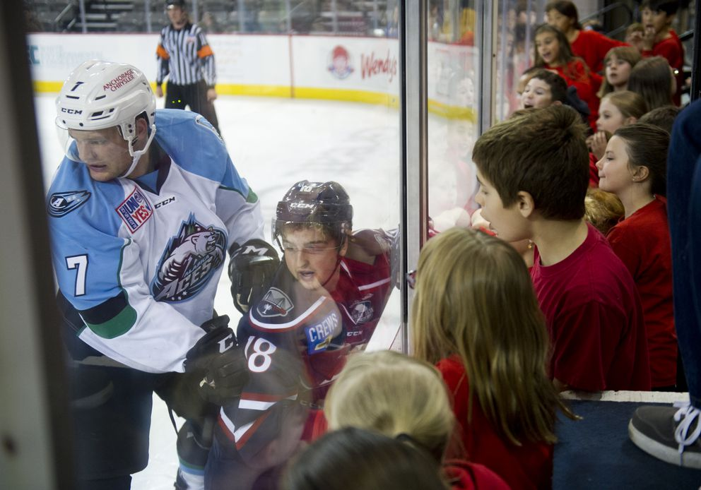 Alaska's Dax Lauwers checks South Carolina's Travis Jeke behind the Aces' goal in the first period. Students from Ravenwood Elementary School, who sang the national anthem, get a good look at the action. (Marc Lester / Alaska Dispatch News)