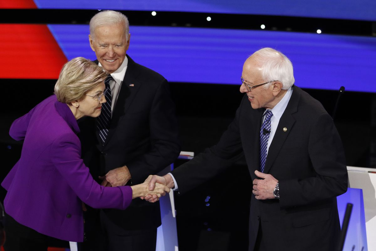 Democratic presidential candidates Sen. Elizabeth Warren, D-Mass., left, and Sen. Bernie Sanders, I-Vt., right greet each other as former Vice President Joe Biden, watches Tuesday, Jan. 14, 2020, before a Democratic presidential primary debate hosted by CNN and the Des Moines Register in Des Moines, Iowa. (AP Photo/Patrick Semansky)