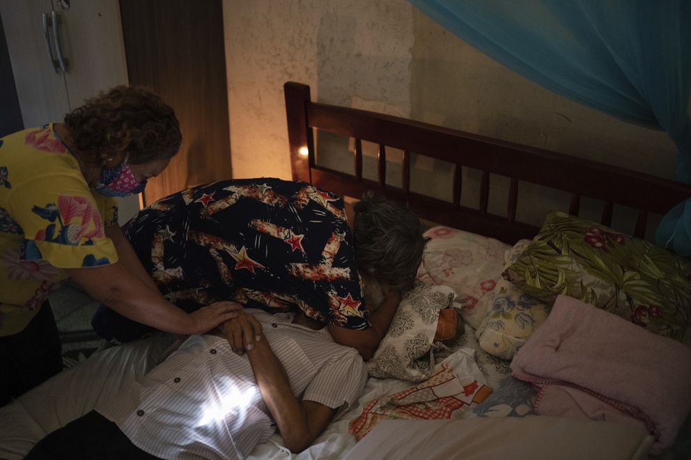 Relatives mourn over the body of Luis da Silva, 82, who had pre-existing health conditions and died at home after suffering from shortness of breath in Manaus, Brazil, Sunday, May 10, 2020. Per capita, Manaus is Brazil's major city hardest hit by COVID-19. (AP Photo/Felipe Dana)