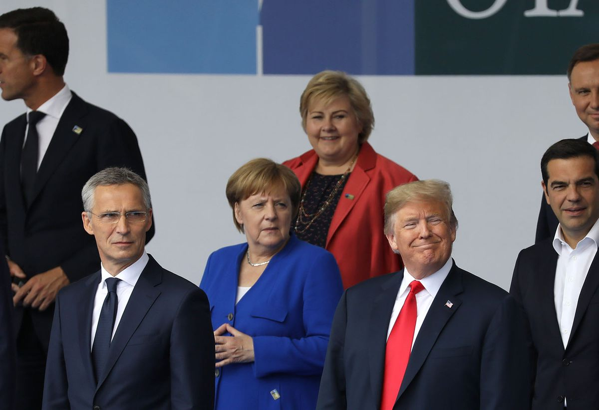 President Trump, front right, German Chancellor Angela Merkel, center, and NATO Secretary General Jens Stoltenberg, left, stand for a photo during the NATO summit in Brussels on Wednesday. Bloomberg photo by Marlene Awaad