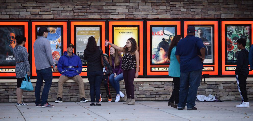 "Martin Sensmeier and family make photos next to the movie poster for ""The Magnificent Seven"" in Anchorage on Friday. (Bob Hallinen / Alaska Dispatch News)"