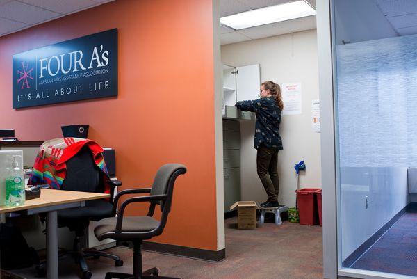 Rachel Swenarton, a volunteer from Jesuit Volunteer Corps Northwest, stocks drawers and shelves of Four A's syringe exchange room. (Marc Lester / Alaska Dispatch News)