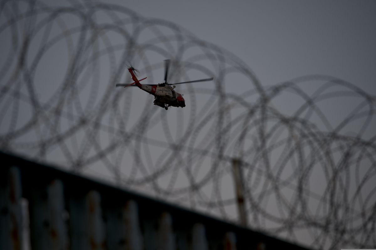 A U.S. Coast Guard helicopter patrols the area near the border fence in Tijuana, Mexico, Sunday, Nov. 18, 2018. While many in Tijuana are sympathetic to the plight of Central American migrants and trying to assist, some locals have shouted insults, hurled rocks and even thrown punches at the migrants. (AP Photo/Ramon Espinosa)